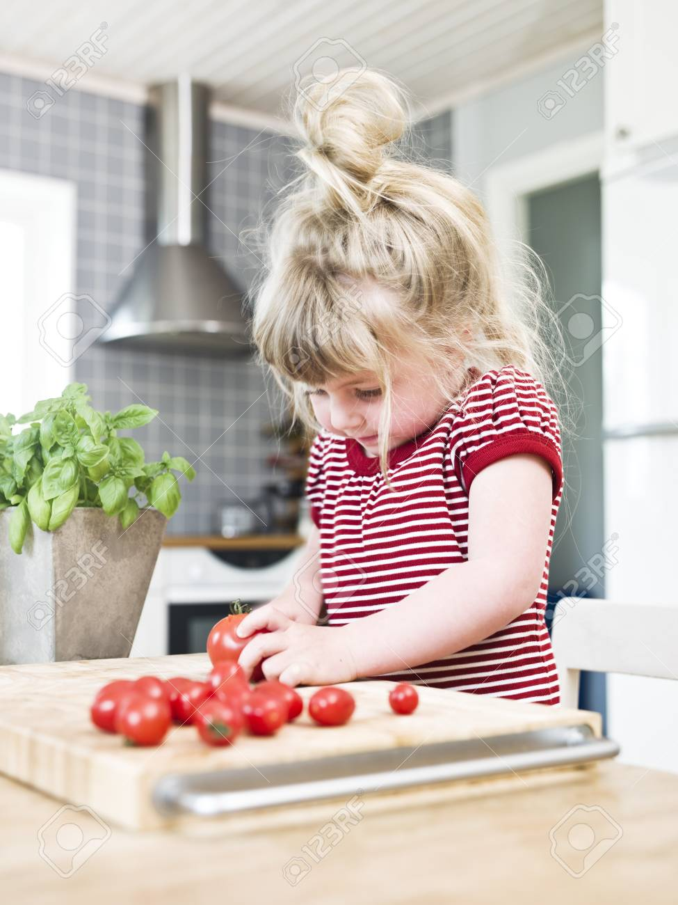 Young girl cutting tomatoes in the kitchen Stock Photo - 7199542