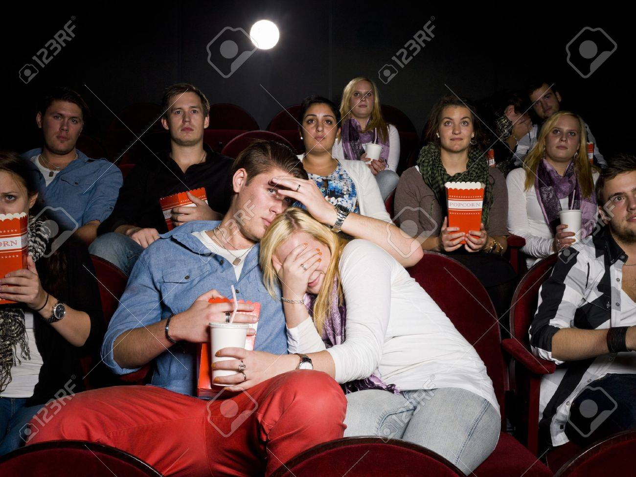Young Scared Couple at the Movie Theater eating popcorn Stock Photo - 10740778