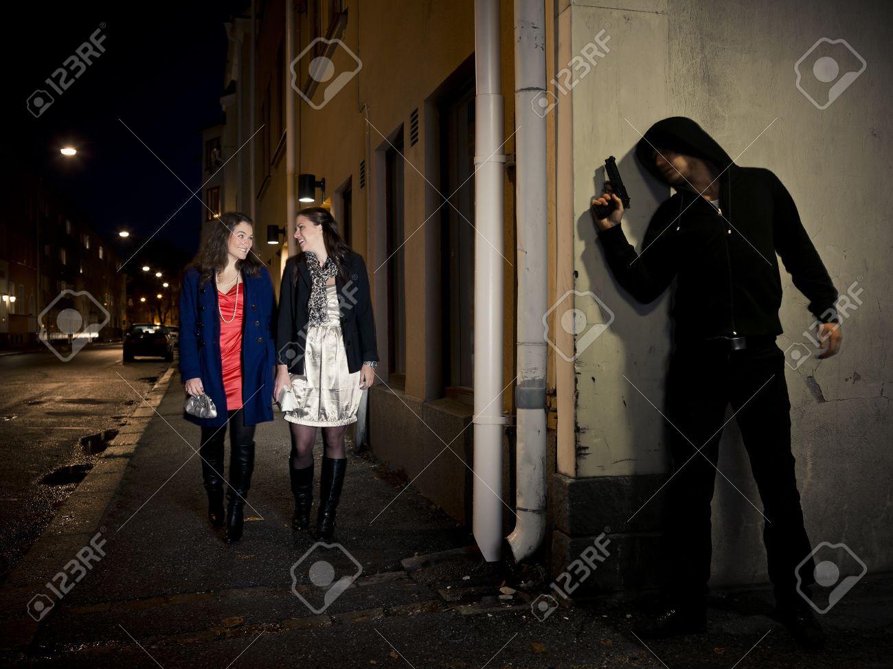 Hooded man stalking two women behind a corner holding a gun Stock Photo - 11223865