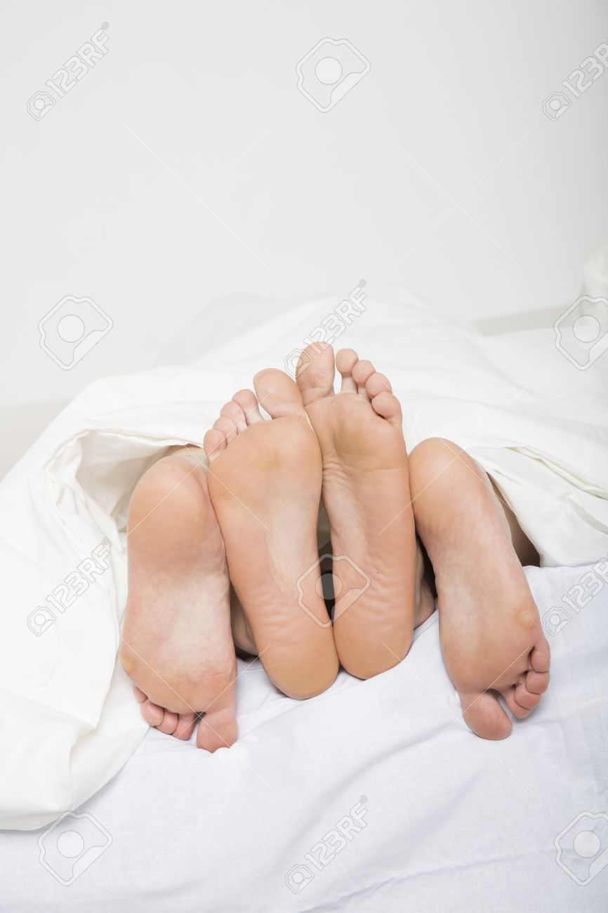 married couples feet in bed stock photo
