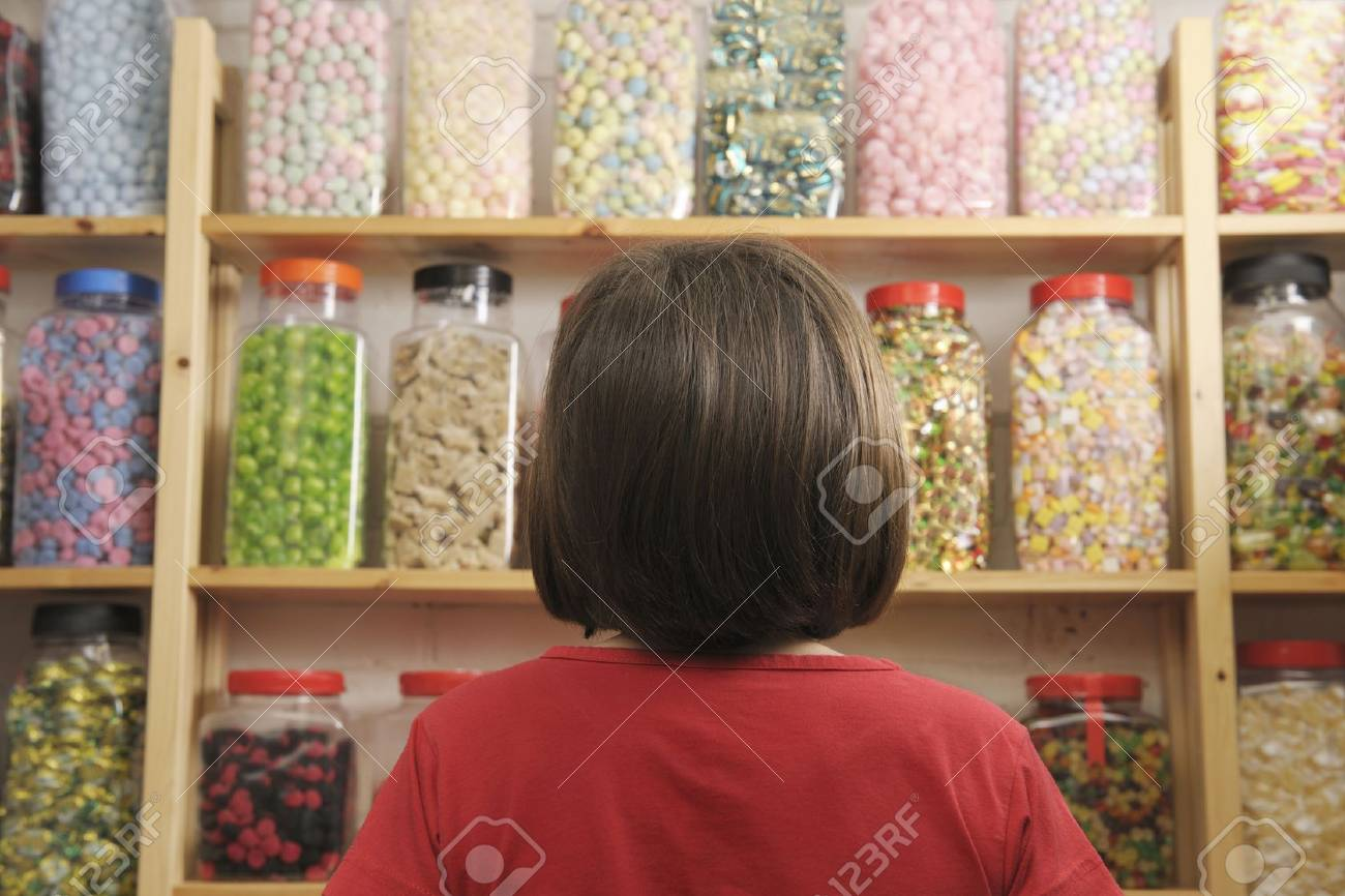 young girl looking at rows of sweets in shop Stock Photo - 4542076