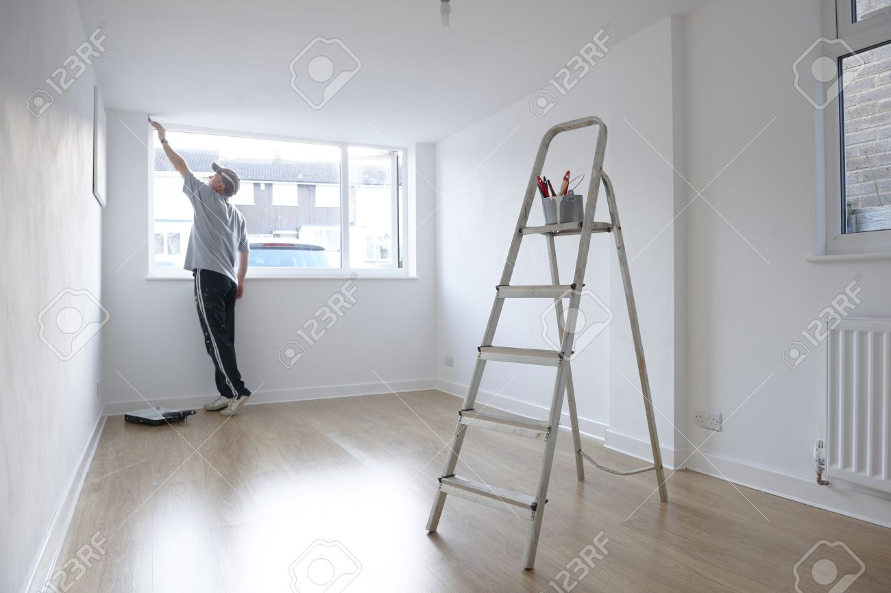 man decorating a room with ladder and paint pot in foreground Stock Photo -  26036127