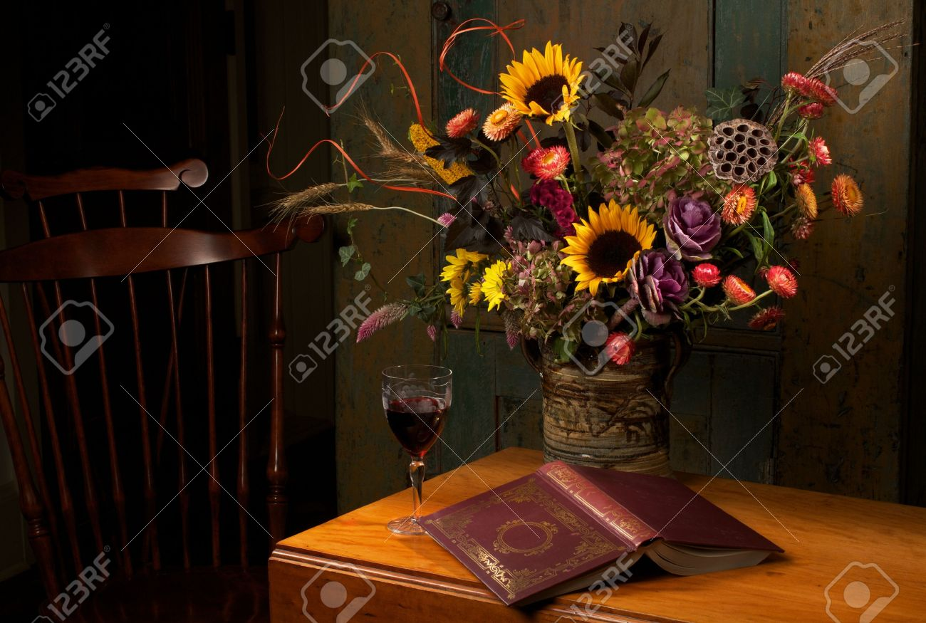 Autumn still life with flowers in handmade stoneware vase, goblet of red wine, and gold embossed leather bound book on antique wooden drop leaf table and Windsor chair. Low key, dark background, copy space. Stock Photo - 14551551