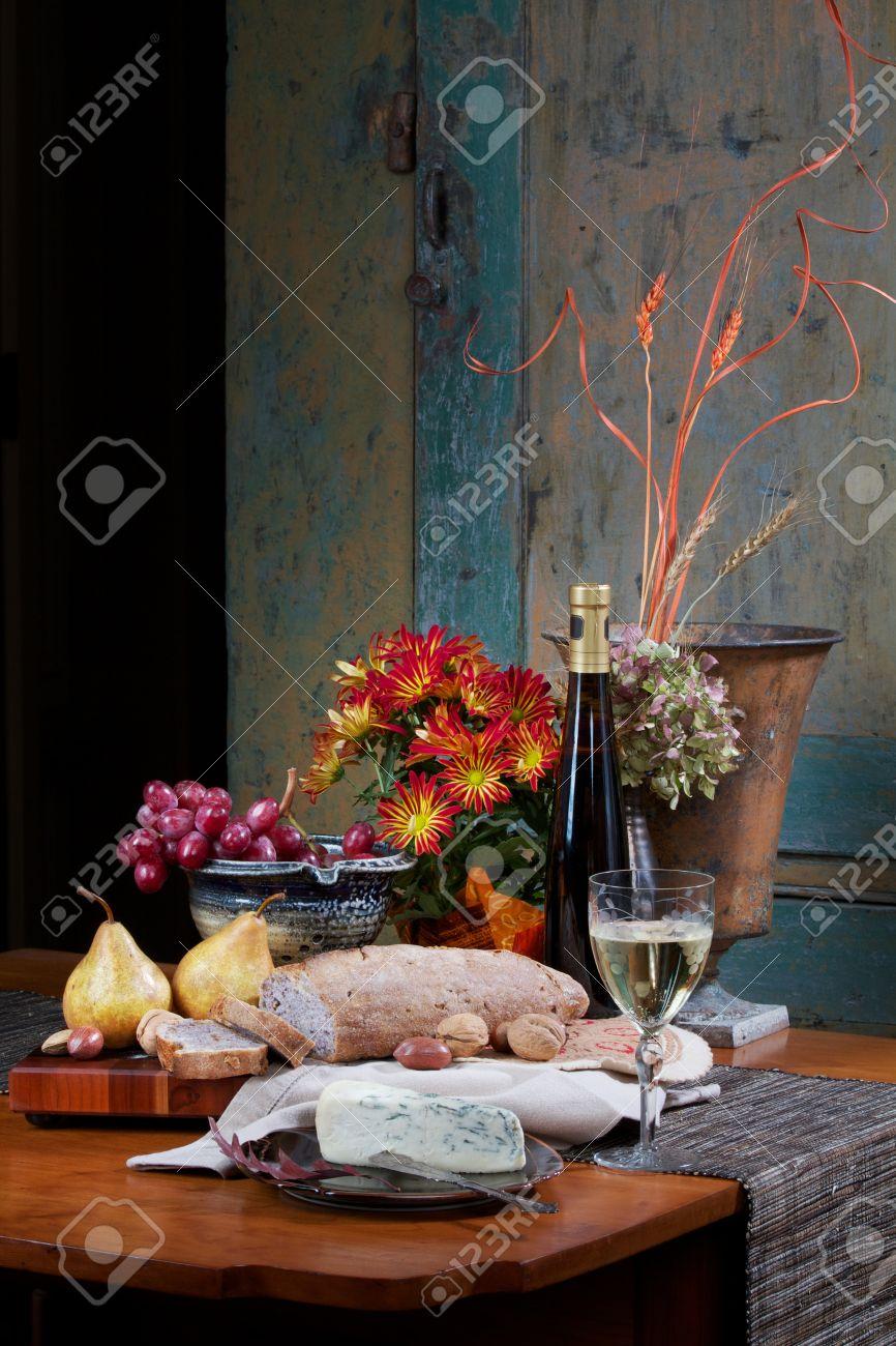 Stillleben Auf Antikem Tisch Ahorn Mit Walnuss Brot, Gorgonzola, Bosc  Birnen, Nüsse, Roten Trauben Und Weißwein. Blumen, Keramik Schale, Silber  Messer Und ...