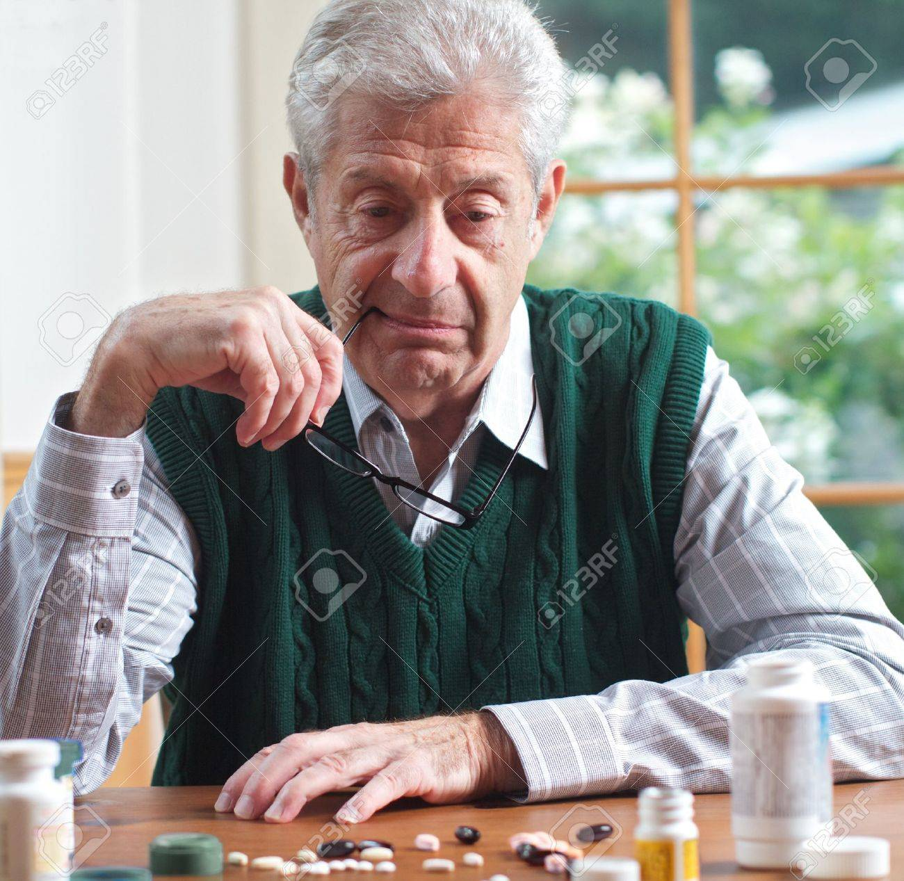 Senior man with glasses in hand looks thoughtfully at many pills on table in front of him  Focus on man  Frontal view, square format, green and white color palatte Stock Photo - 14546619