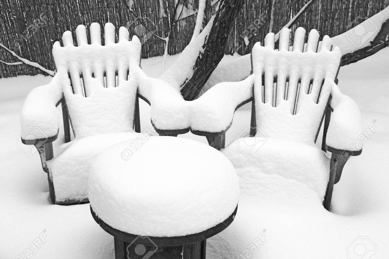 deep fluffy snow covers outdoor garden table and two rustic chairs