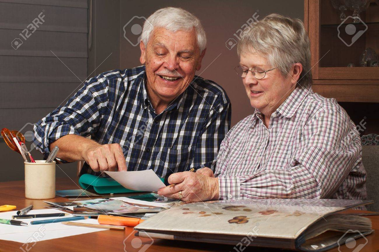 Happy senior married couple sharing memories while  working on family photo  album together. Horizontal format. Stock Photo - 14570371