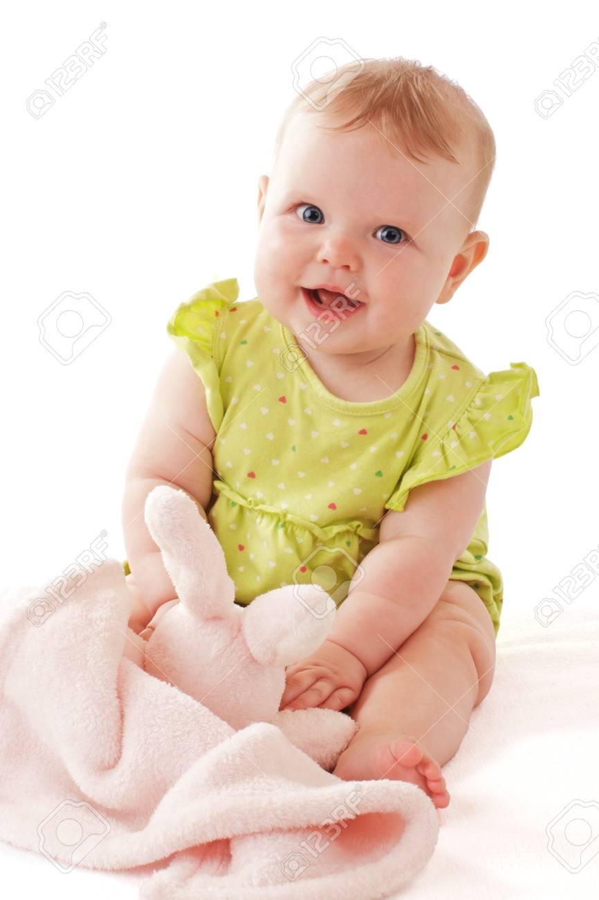3bd9e851e627e3 Lachende baby meisje met grote blauwe ogen zitten en spelen met een zachte  bunny deken.