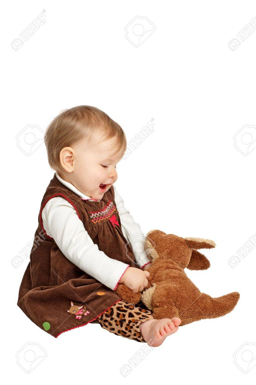 8492401e9b51 Delighted Smiling Baby Girl Sits Sideways Holding Stuffed Toy ...
