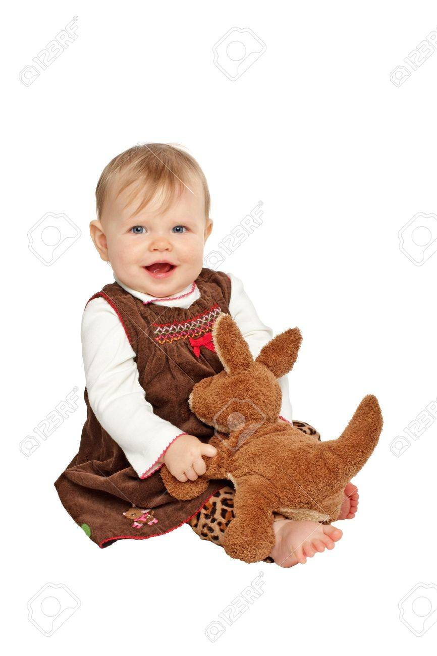 Smiling Baby Girl Sits And Plays With Brown Stuffed Toy Kangaroo