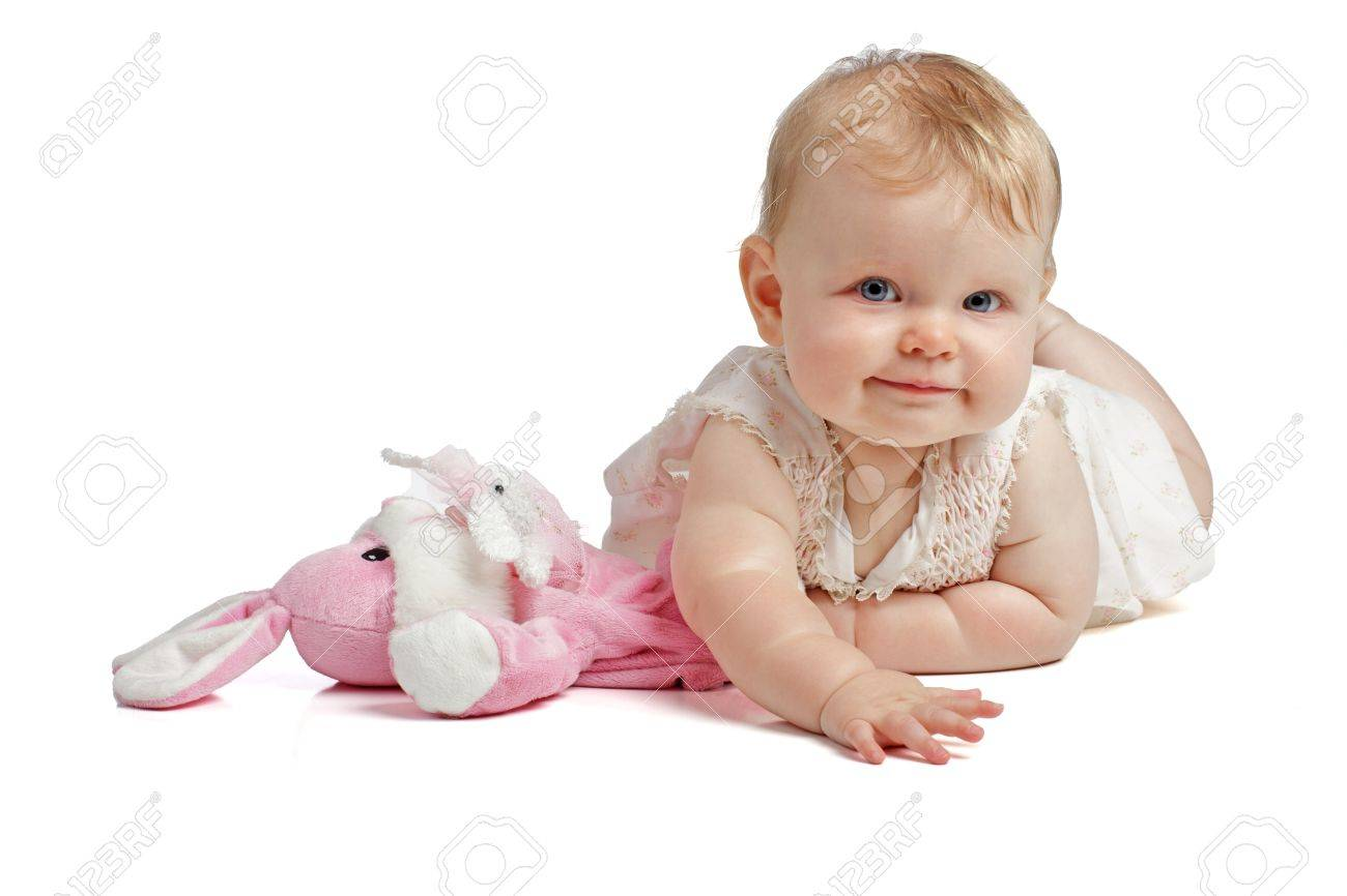 Smiling eight month old baby girl lies on tummy beside pink toy rabbit she wears