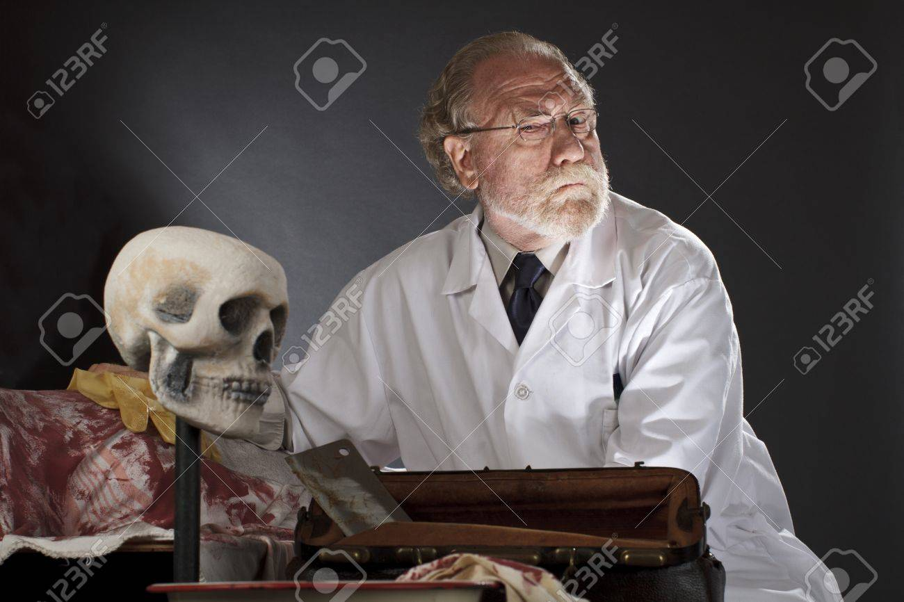 Evil doctor with surgical tools and bloody corpse  Sinister expression, dark background with dramatic low angle spot lighting  Horizontal, copy space Stock Photo - 16963210