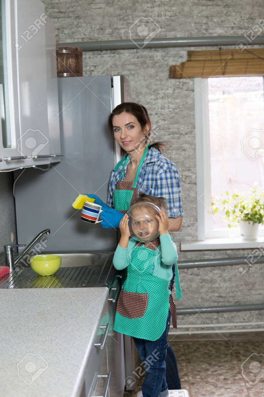 Mom And Daughter Are Washing Dishes In The Kitchen, A Woman And A ...