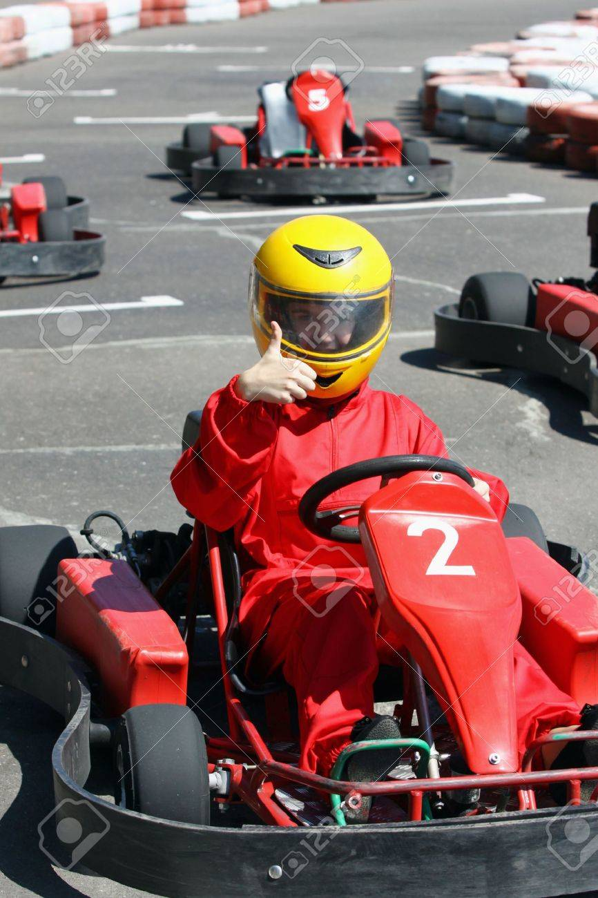A smiling young racer shows ok  Go-carting