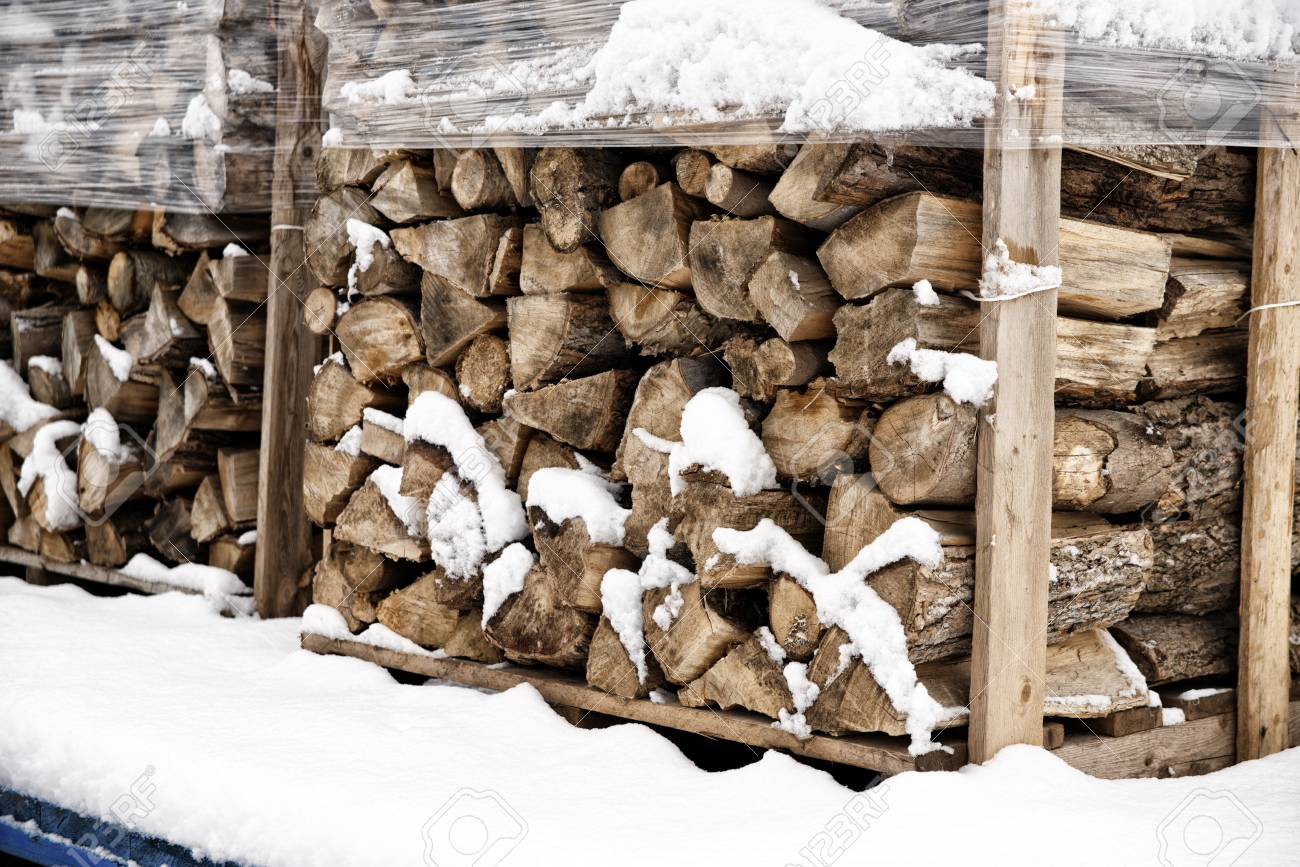 Stack Of Chopped Firewood Covered In Winter Snow Wood Cut And