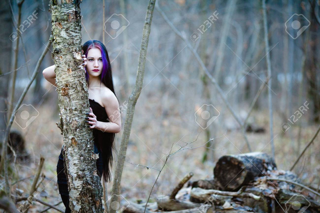 portrait of the gothic woman in the dark winter forest stock photo
