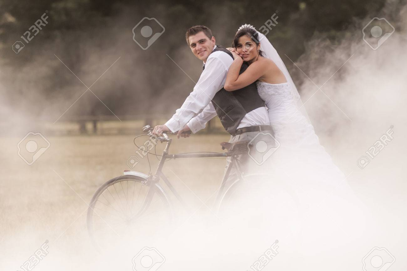Newly wed bride and groom riding a vinatage bicycle through misty field - 37163861