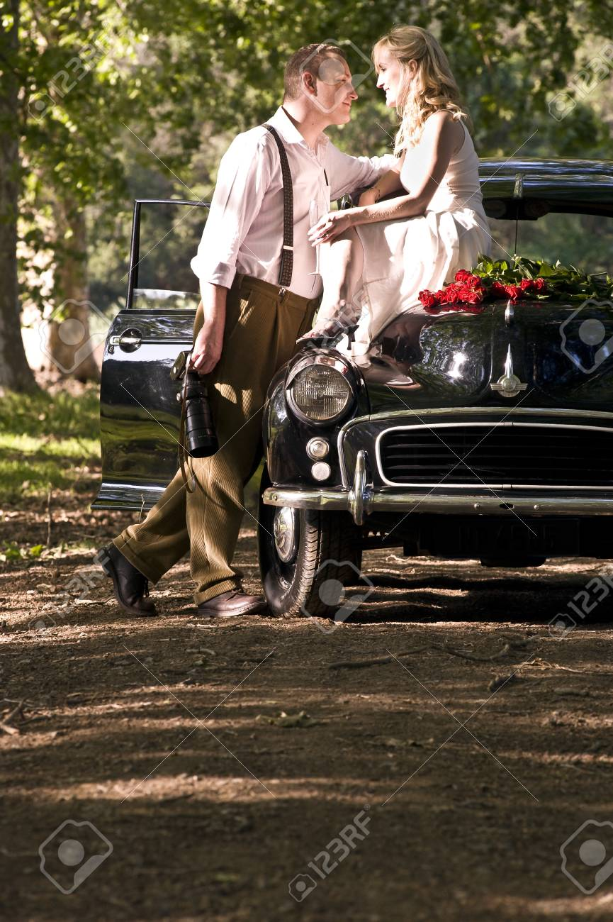 Happy attratcive couple outdoors with vintage car and red roses - 79148398