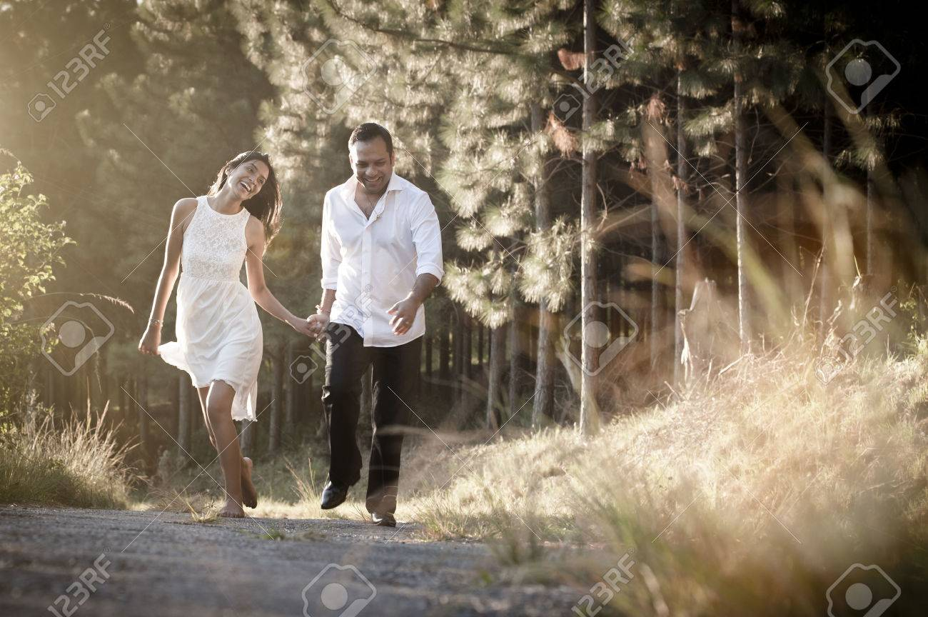 Happy Indian couple running along dirt road with golden light through long grass - 37163803