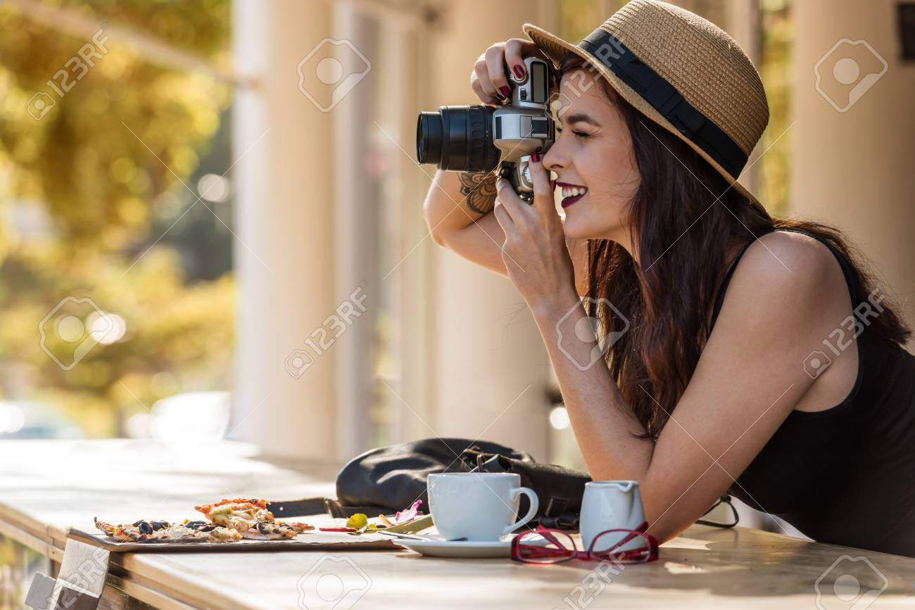 young beautiful traveler happily taking photos with camera at cafe - 61927746