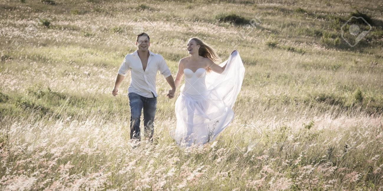 Couple walking together holding hands in an open field. - 79148433