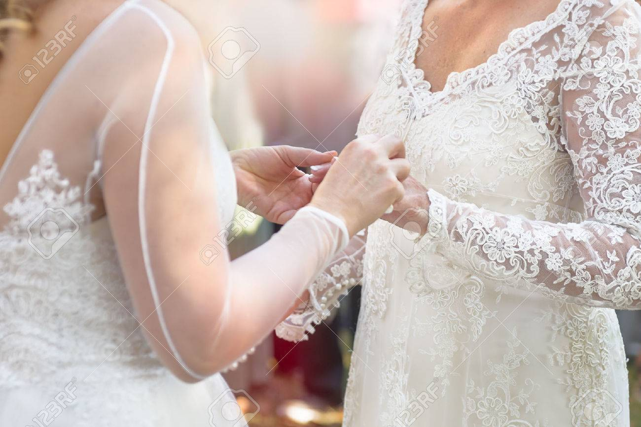 Same bride places ring on finger during wedding ceremony - 62048393