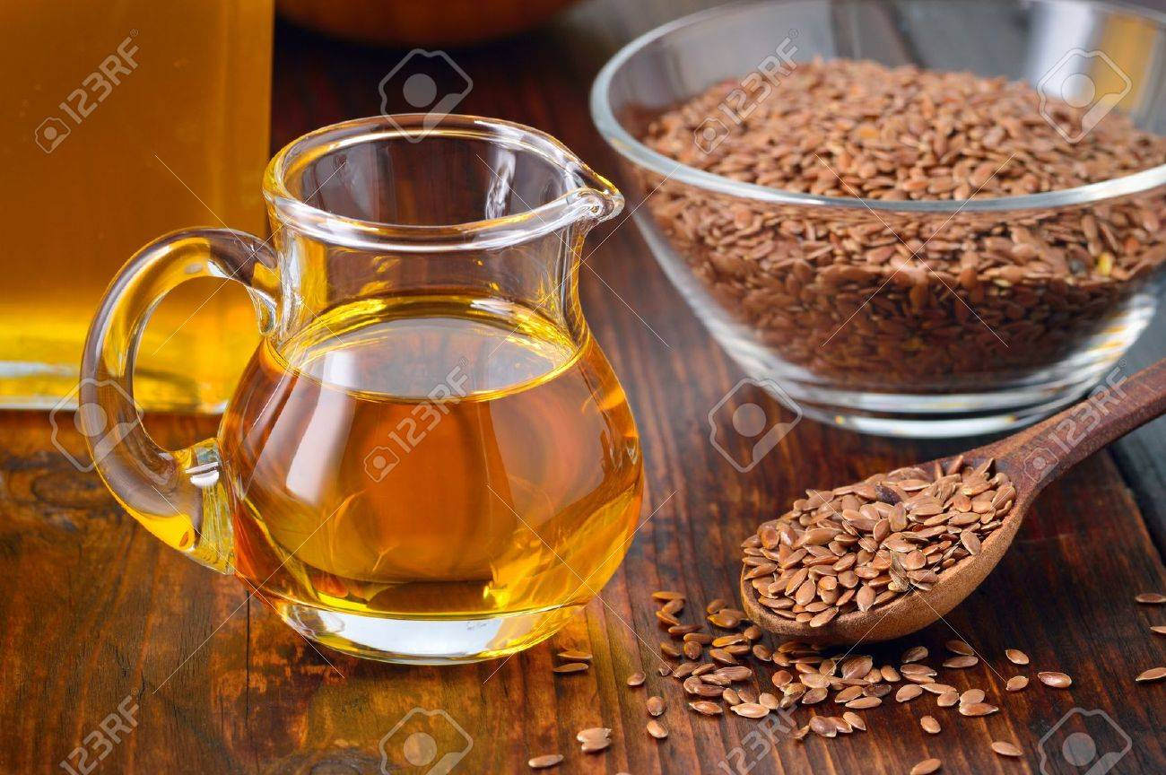 Brown Flax Seeds On Spoon And Flaxseed Oil In Glass Jug On Wooden
