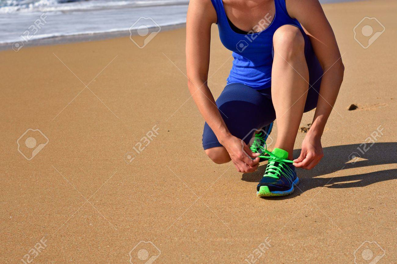 Running shoes - closeup of woman tying shoe laces. Female runner jogging getting ready for jogging on the ocean beach. Outdoor sports. Active lifestyle. - 50418537