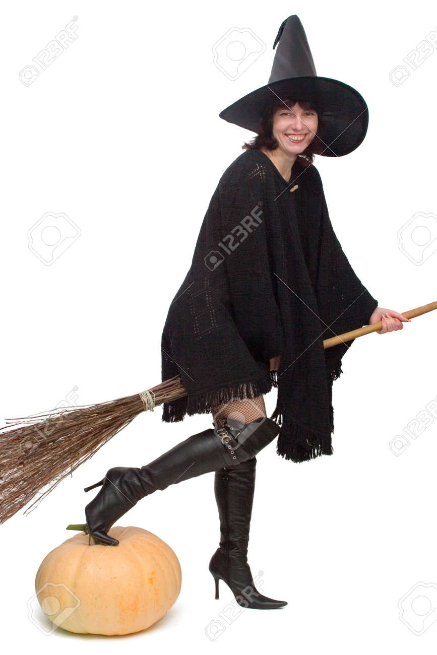 Pretty witch bestridden a broom and ready to fly away, with a toe on large pumpkin Stock Photo - 542320