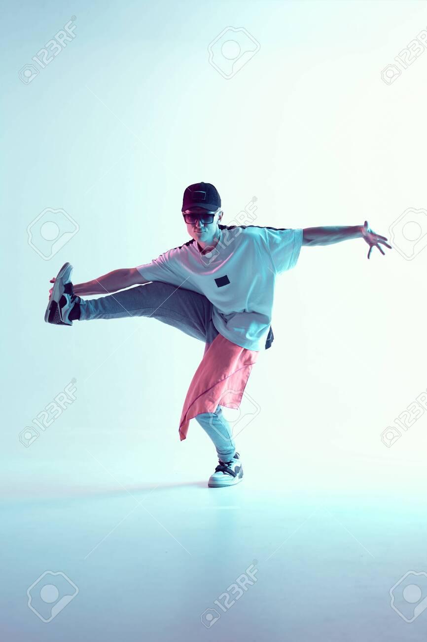 Guy dancing contemporary dance in studio. Neon light blue background. Acrobatic bboy dancer. Break dance lessons. - 152643770