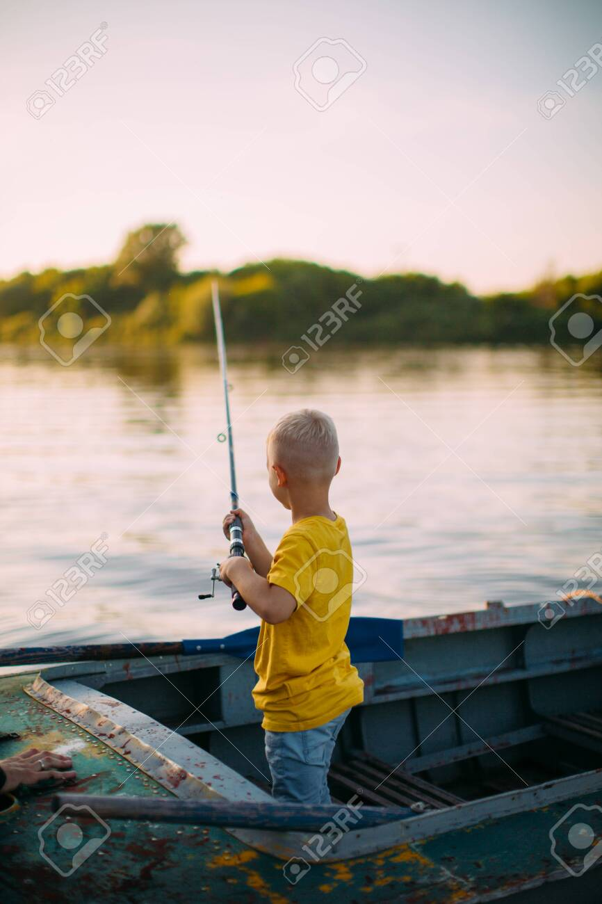 Baby boy fishing from boat on river in summertime, back view - 153551202
