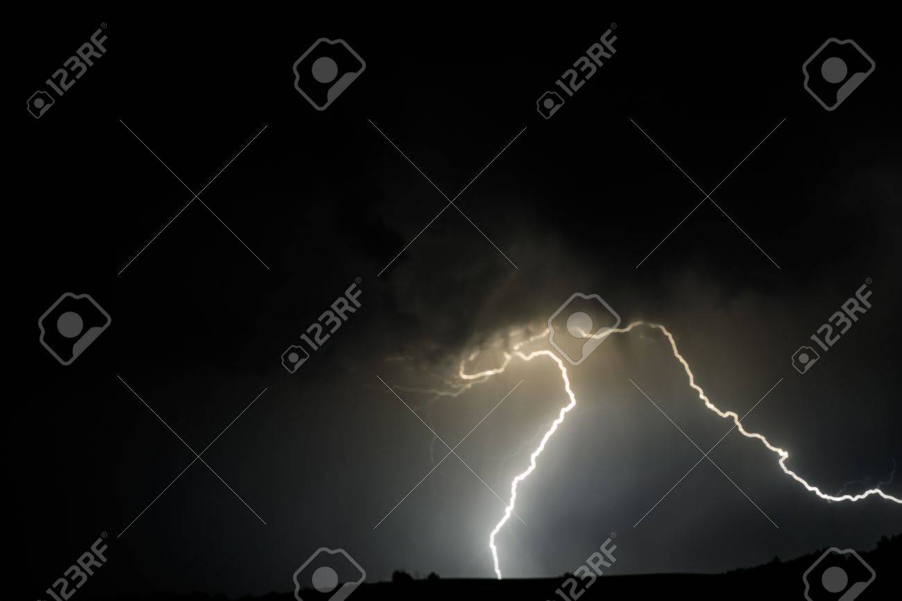 A stream of lightning bolts erupts from a thunder cloud over. Stock Photo - 21528228