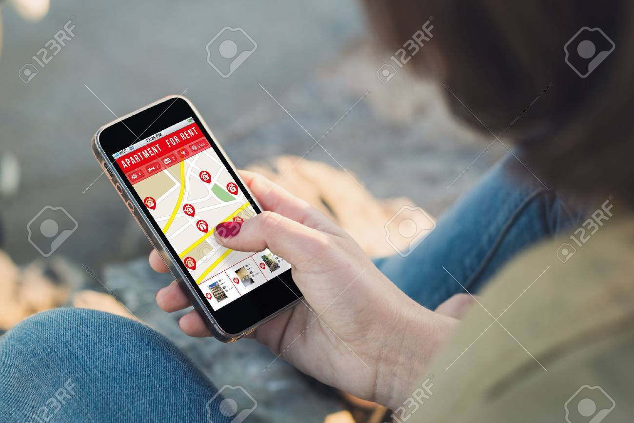 woman holding a smartphone with apartment search on screen. all
