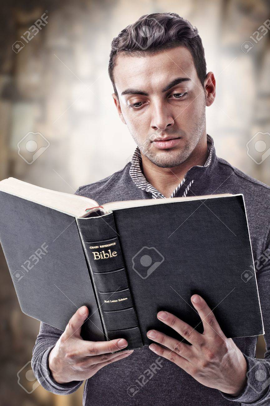 Portrait of a young man reading the Holy Bible Stock Photo - 11894450