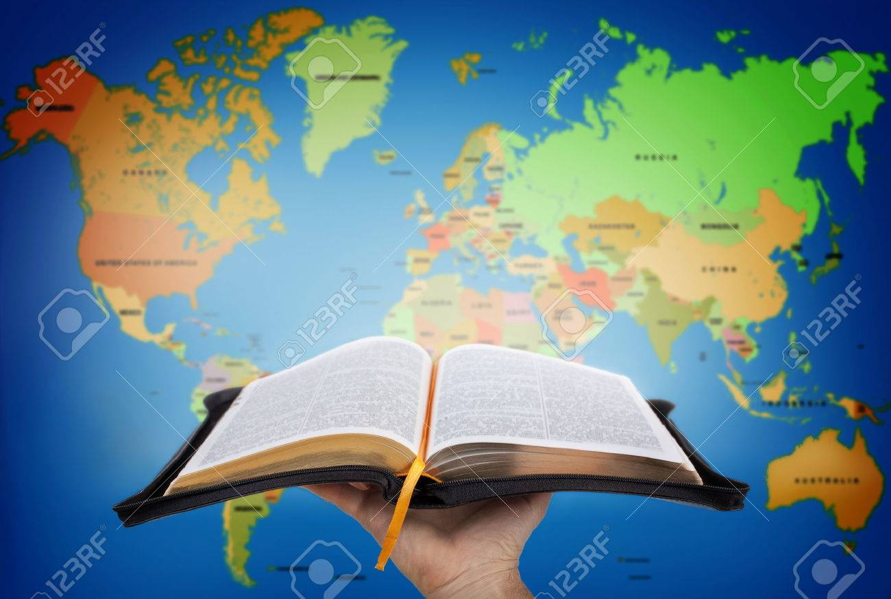 Hand Showing The Holy Bible Against World Map Stock Photo, Picture