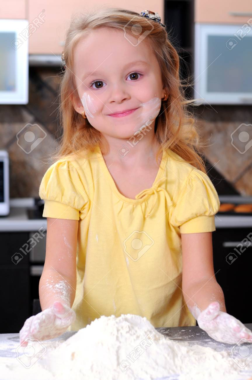 Cute blond little girl making bread in the kitchen Stock Photo - 20815855