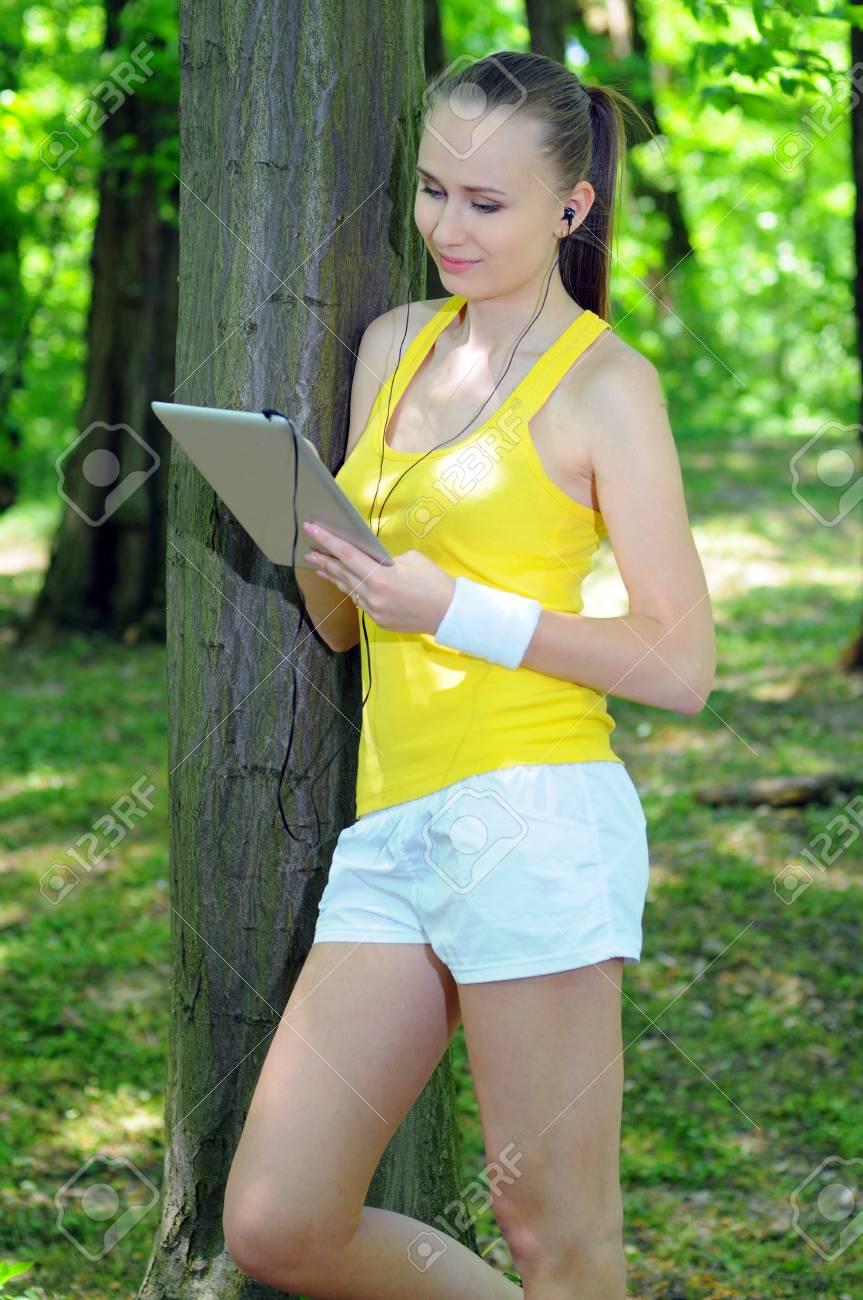 Young woman with tablet doing fitness in city park Stock Photo - 20818496