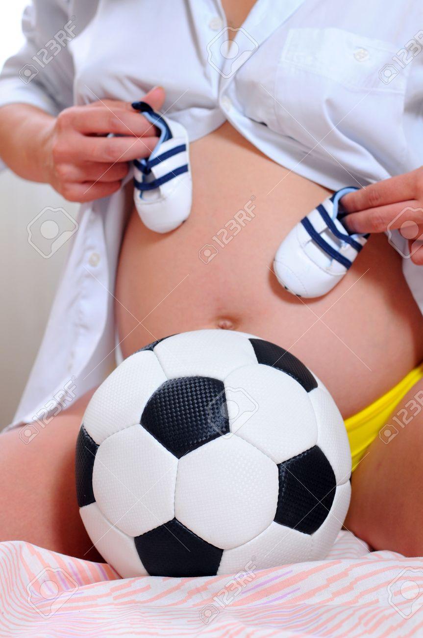 fb6f352c793cb Foto de archivo mujer embarazada joven con un balón de fútbol zapatos  deportivos para el bebé