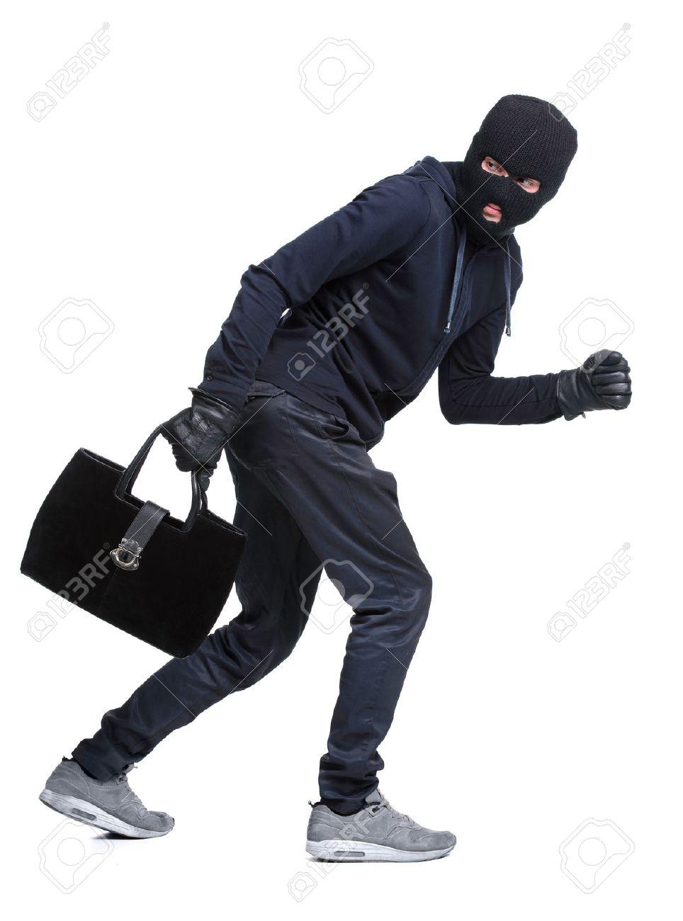 Portrait of running male burglar with a handbag. Isolated on white background Stock Photo - 28277601