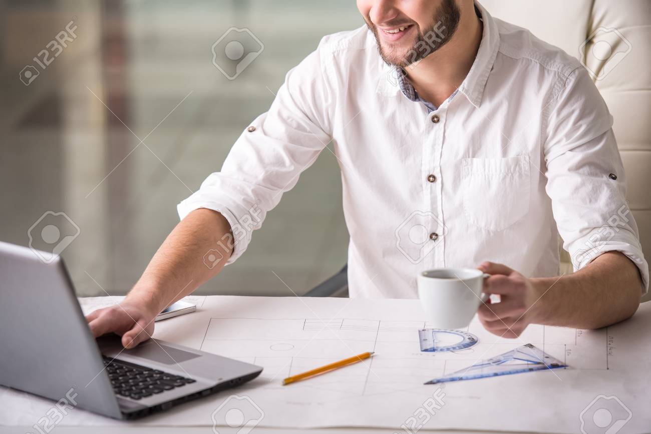Young architect with blueprint is drinking coffee while siting stock photo young architect with blueprint is drinking coffee while siting in the office malvernweather Choice Image