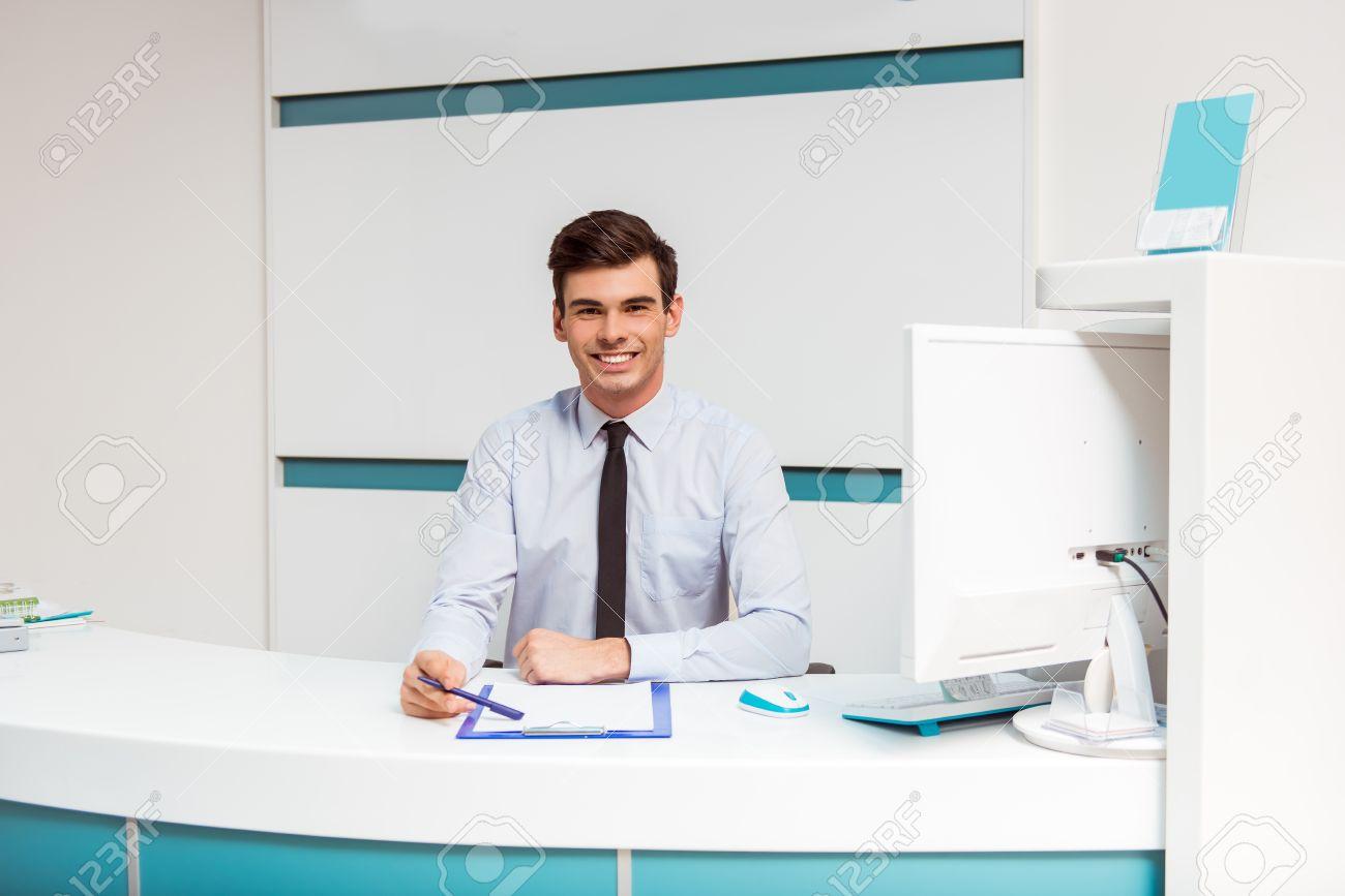 Portrait d un jeune homme souriant avec réceptionniste au bureau