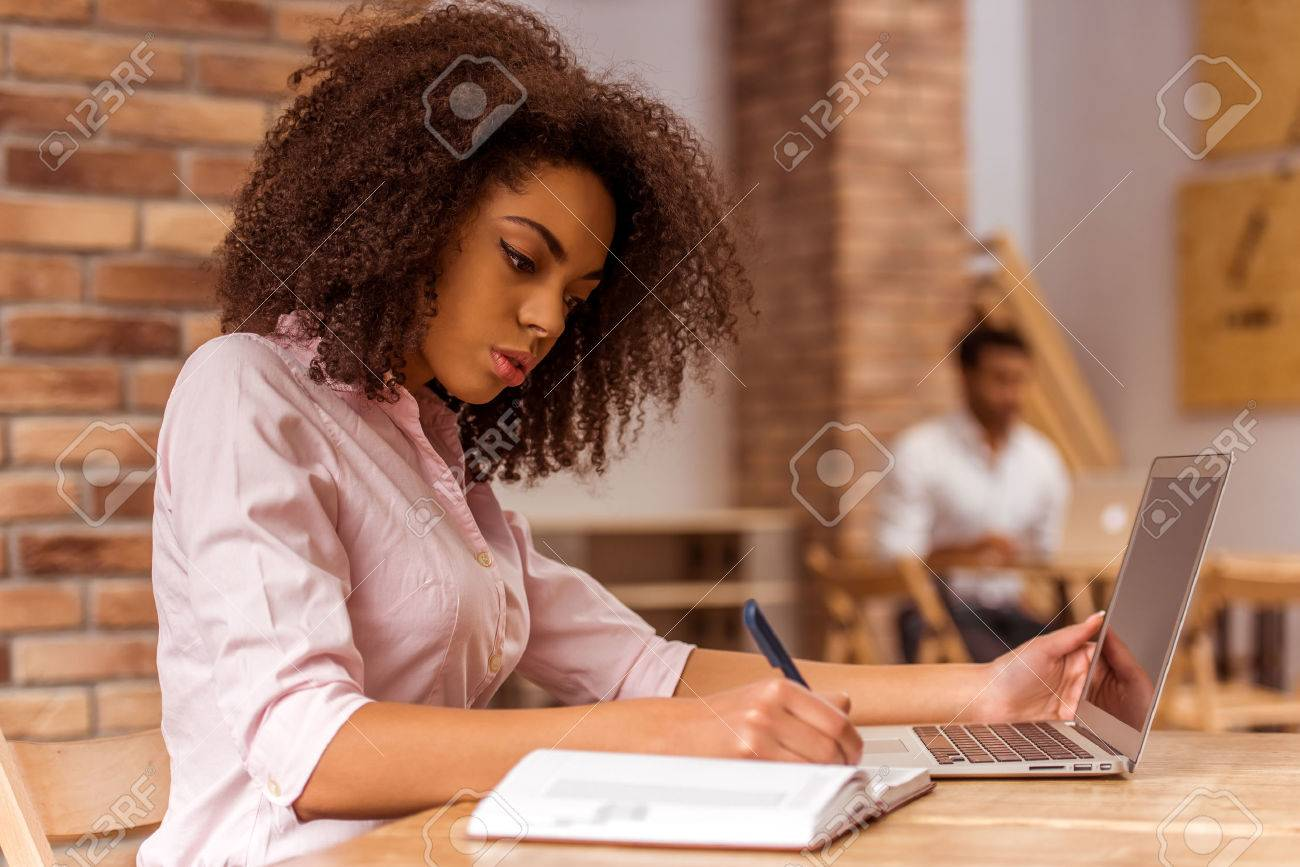 Young beautiful Afro-American businesswoman using laptop and writing in notebook while studying in cafe - 51766485