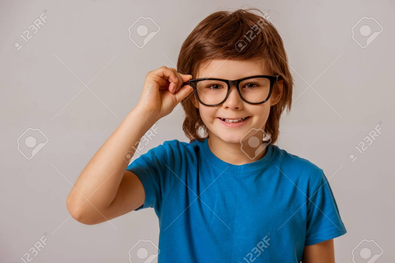 e464008a12b6 Portrait of a cute little boy in a blue t-shirt and eyeglasses looking in