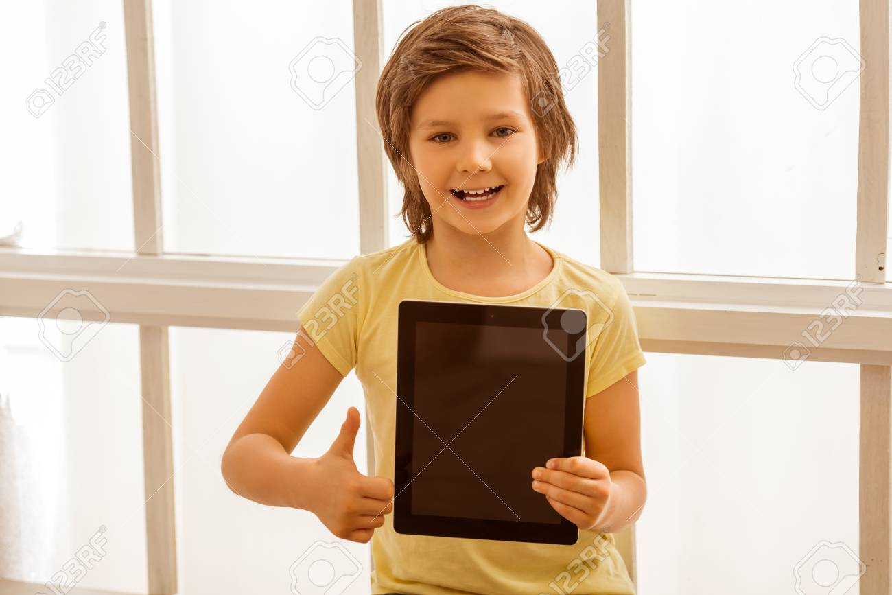 Beau Petit Garçon Tenant Une Tablette Montrant Le Signe Ok
