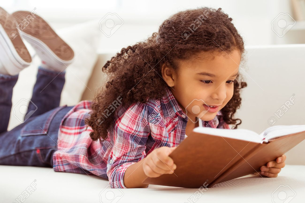 Cute little Afro-American girl in casual clothes reading a book and smiling while lying on a sofa in the room. - 52354895