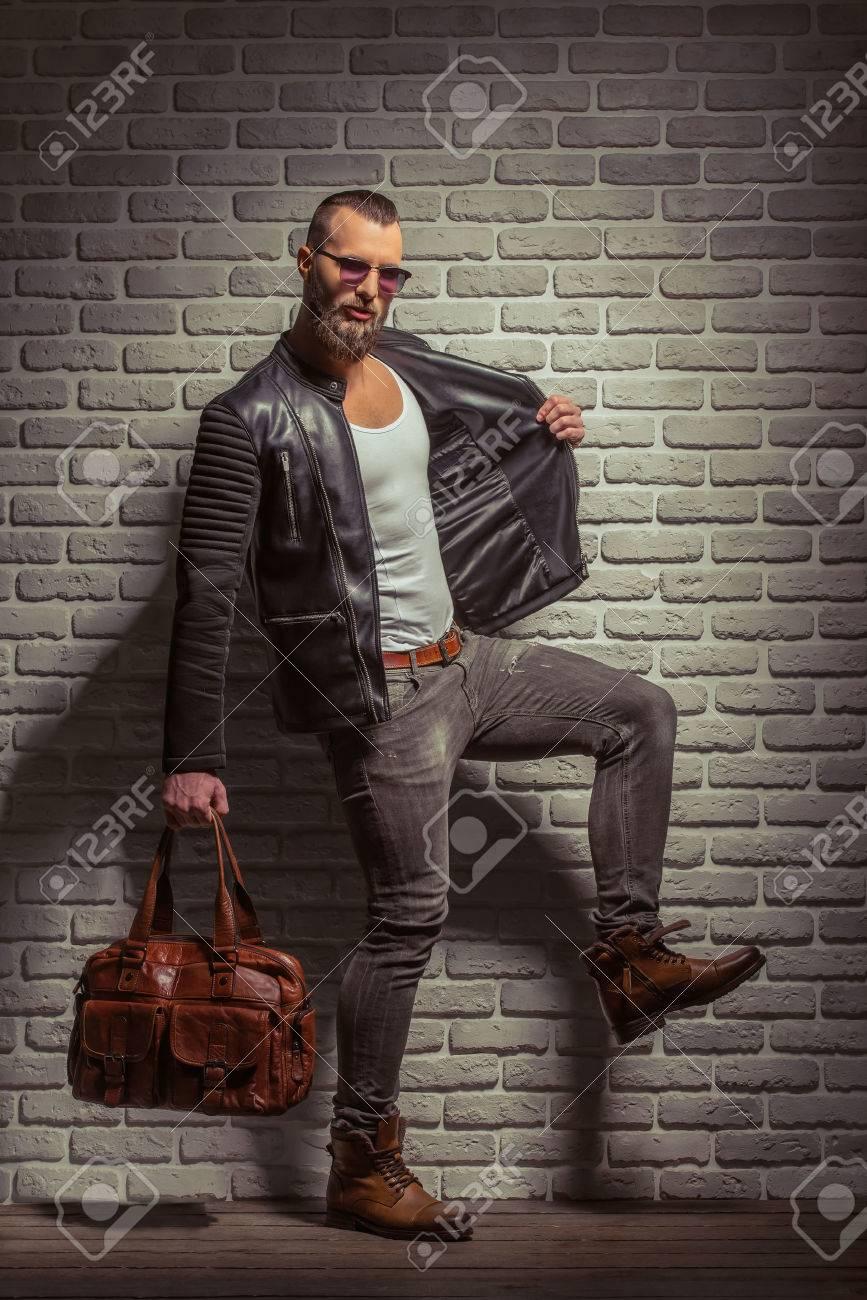 super qualité style actuel rétro Homme élégant avec une barbe en veste de cuir et lunettes de soleil tenant  un sac en cuir brun, debout contre le mur de briques