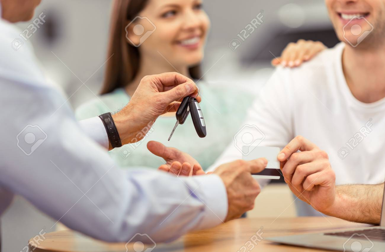 Young couple is smiling while buying a car, middle aged worker of a motor show is giving keys, close-up - 53130635