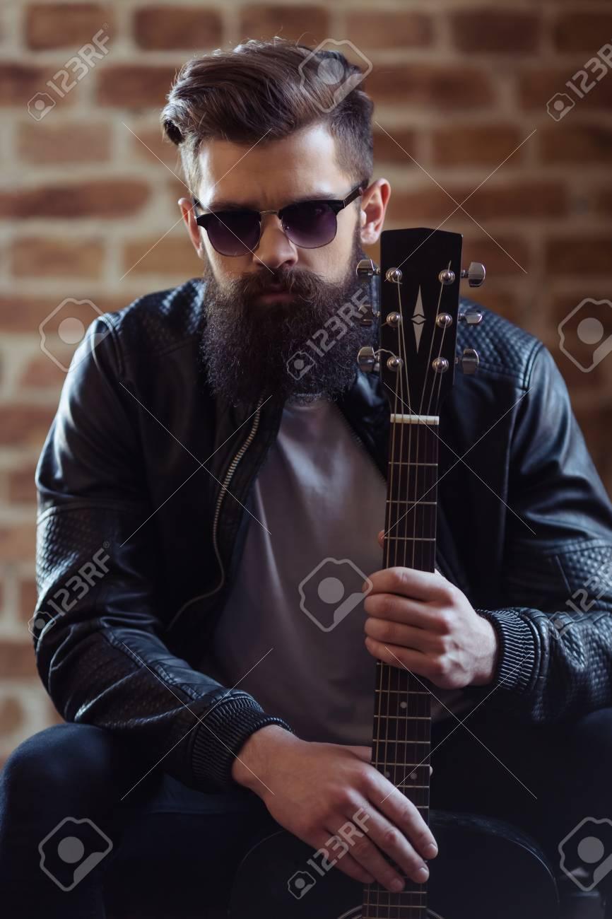Elegante giovane uomo barbuto in giacca di pelle nera e occhiali da sole è in possesso di una chitarra e guardando la fotocamera, seduto contro il