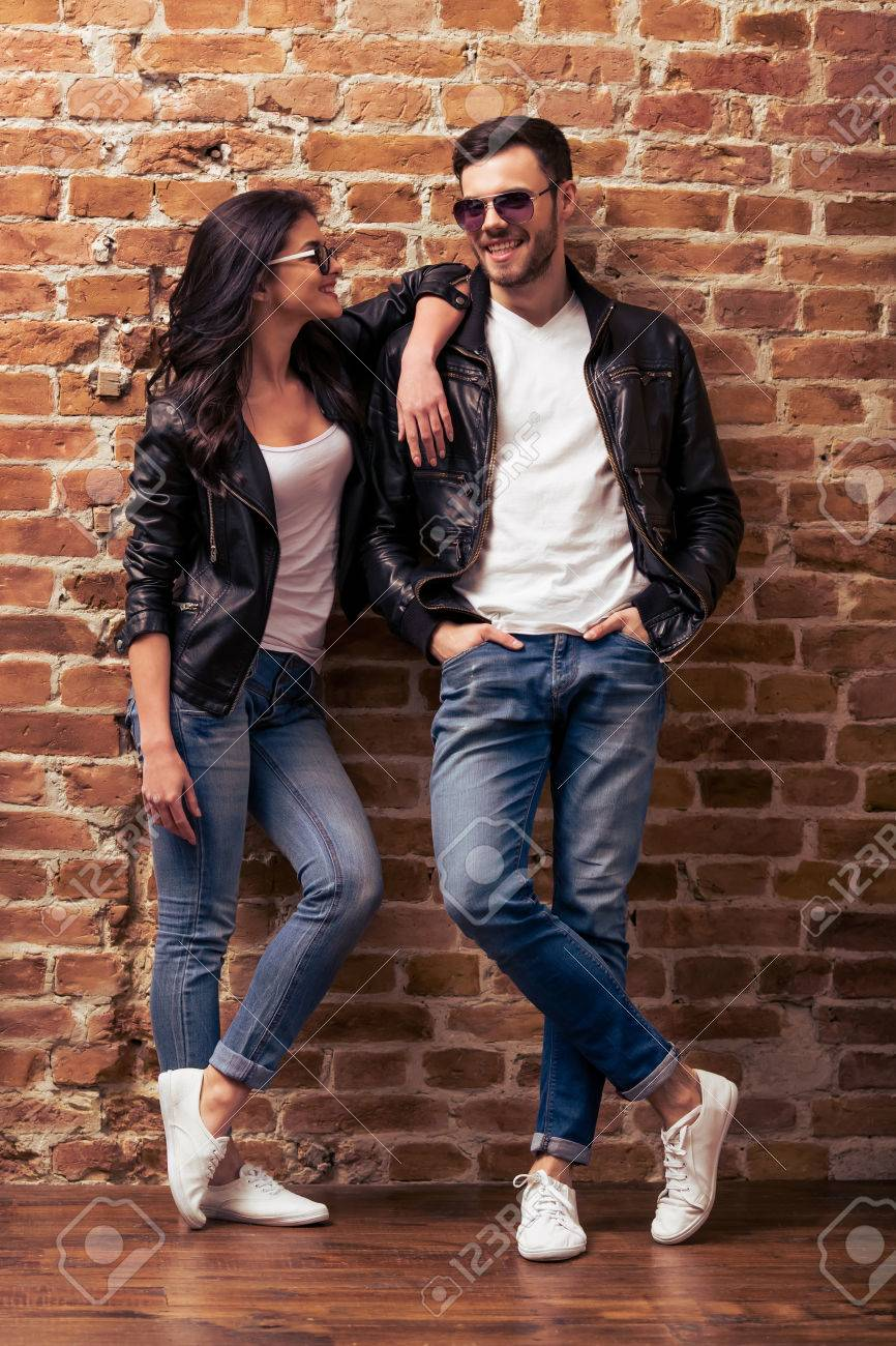 Cool Beautiful Young Couple In Leather Jackets And Sunglasses Is Looking At Camera Posing And