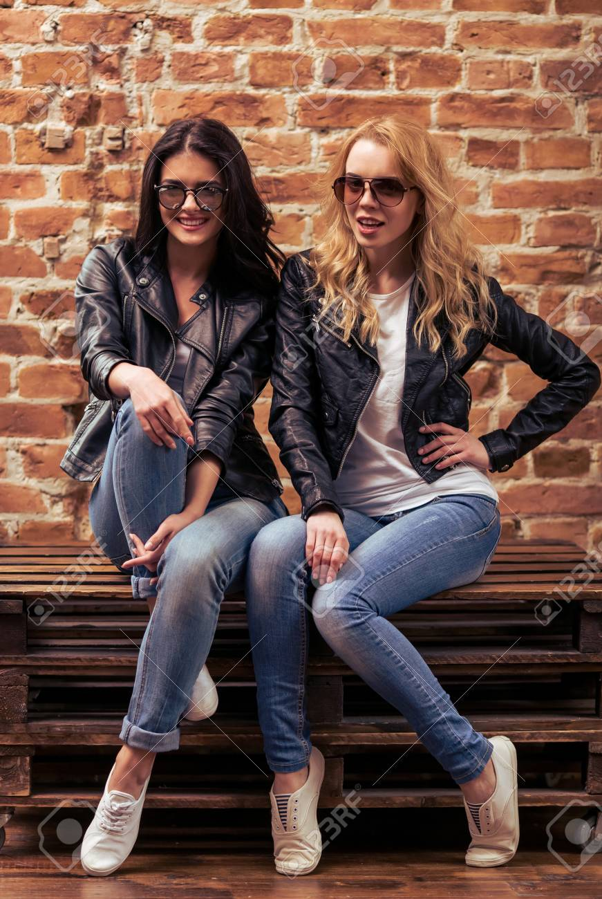 Cool Beautiful Young Girls In Leather Jackets And Sunglasses Are Looking At Camera And Smiling
